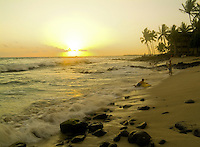 Two boys play with body boards in the beautiful golden surf at Hano beach, Kona with a glowing sunset reflected in the waves.