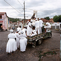 Worshippers from the branch, or nation (nacoe), of Candomble known as Candomble do Caboclo. The term Caboclo, aside from being a term to describe a person of mixed Brazilian Amerindian and European descent, is also used as an alternate term for certan orixas (gods) of the Candomble religion. The caboclo, that can be seen here on the truck, is also an orixa.