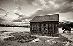Decaying structures sit in a snow-covered field in Central Montana with dark clouds looming overhead.