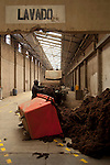 Worker piles on loads of alpaca wool to be washed through an assembly line at an alpaca wool factory in El Alto, Bolivia.