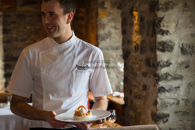 The pastry chef Yves Roland holding one of his creations - a dessert of coconut and grapefruit at Panache Restaurant located in the Auberge Saint Antoine. The menu features local meats and produce. The Auberge Saint Antoine hotel located in Quebec City's Old Port and across the street from the St. Lawrence district was built on an archeological site.  The archeological fragments and finds are incorporated into wall displays throughout the hotel.
