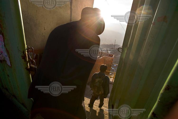 People walk through a back street between houses in El Alto.