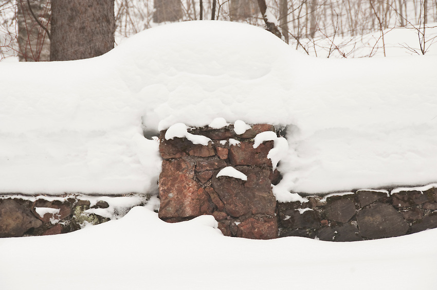 A stone fence is piled with snow during winter on the Keweenaw Peninsula near Copper Harbor Michigan.