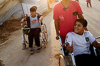 Two boys in wheelchairs play with friends in the Zaatari Refugee Camp. Approximately two million people have fled the conflict in Syria. At least 130,000 of them live in Zaatari Refugee Camp, although it was designed to house 60,000, and a further 2,000 people arrive each day.