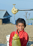A boy fills a container with water at a community spigot in Makaising, a village in the Gorkha District of Nepal hit hard by a devastating 2015 earthquake.