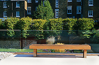 A long wooden bench stands next to the glass wall which act as a safety barrier along the roof terrace with  pleached hornbeams in the distance