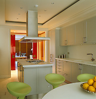 A well-equipped contemporary kitchen is connected to the adjoining dining room by red-lacquered sliding doors