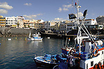 Fishing boats in the harbour of Los Abrigos, restaurants in the background.Tenerife, Canary Islands, Spain.