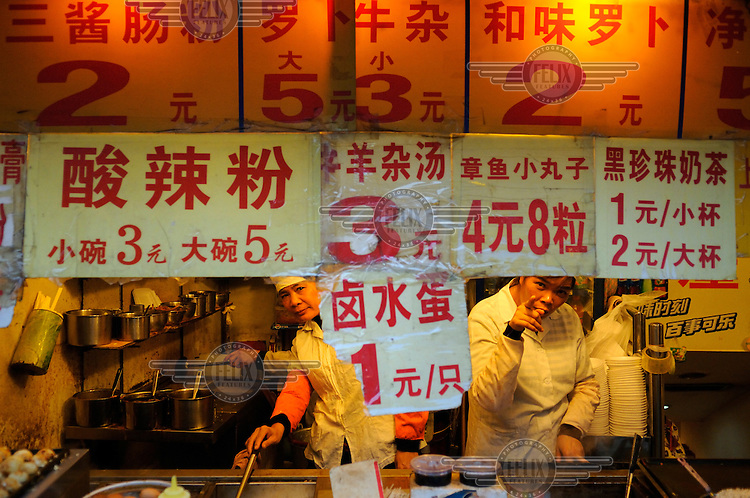 Women working at a cheap fast food stall.