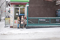 Pedestrians prepare to enter the subway in the Chelsea neighborhood of New York on Tuesday, March 14, 2017. Originally predicted as a blizzard with up to 20 inches of snow the storm has changed its course and only 4 to 6 inches of snow, sleet and rain are expected, accompanied by howling winds of course. (© Richard B. Levine)