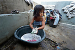"""In the capital of the Philippines, 5-year old Claris Caralos washes clothes in the Manila North Cemetery. Hundreds of poor families live here, dwelling in and between the tombs and mausoleums of the city's wealthy. They are often discriminated against, and many of their children don't go to school because they're too hungry to study and they're often called """"vampires"""" by their classmates. With support from United Methodist Women, KKFI provides classroom education and meals to kids from the cemetery--including this girl--at a nearby United Methodist Church."""