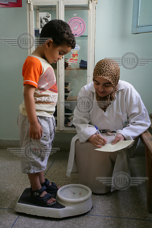 Health worker weighing a young boy at a health centre.