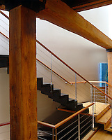 A contemporary wood and steel staircase is situated under the massive original beams of a Tribeca loft apartment