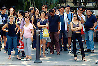Singapore. Downtown. Town center. Orchard Road is mostly a place to shop with rows of modern shopping centres and the location for most international hotels. A crowd of people (men and women) wait for the green light to cross the street on a pedestrian crossing. © 2001 Didier Ruef