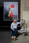 A removals man rests on a collection trolley beneath a fashion model poster in a Mayfair street, London.