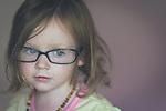 Female child wearing adult glasses