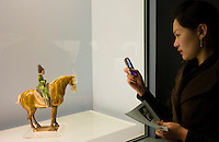 Woman takes a photograph using a mobile phone of an object on display in the Shanghai Museum, China