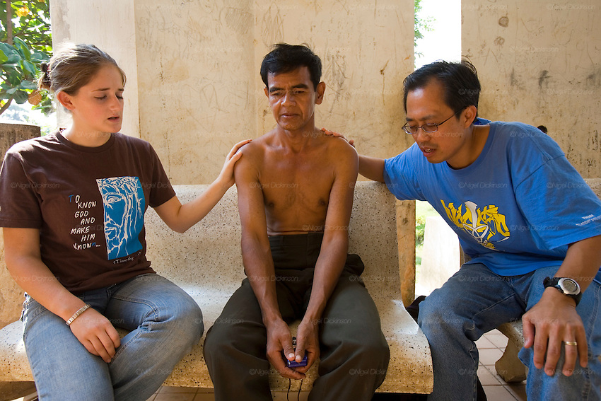 "EVANGELISM AMERICAN STYLE. South East Asia. Battambang, Cambodia. A 'University of Nations' project, registered in Cambodia as a project of the international Christian Evangelical 'Youth With a Mission' (YWAM), run by 'Group Leader' Garth Gustafson. It is a fanatical Evangelist youth movement who use english and sports teachings as a vehicle, together with religious indocrination, to turn buddhist youth and even monks, towards the Christian Bible. Garth preaches quasi-religeous sermons about 'hot and cold' climate types, of Western moral superiority and stronger work ethics, American right obsessions with family and personal responsibility, versus ""primitive people who use smiles to hide their lies"". They preach they ""want to see your (Cambodian) nation change to be a good nation, to glorify God"" but YWAM is a cult-like organisation with right wing and facism roots. The YWAMers force themselves upon AIDS patients in local hospitals, looking for the very sick and dying, offering neither drugs nor food, but instead, prayers about Christian redemption, offer everlasting life, which when rejected by buddhists, they are accused of being ""bitter"" for declining them.///'Youth With a Mission' (YWAM) volunteers redeeming souls at an AIDS hospital clinic in Battambang. Slogan on T-shirt:  To know God and him known"