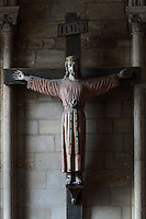 Crucifixion statue of Christ in robes on the cross, 18th or 19th century, originally from the Collegiale Sainte Balsamie, in the Basilique Saint Remi or Abbey of St Remi, Reims, France. The 11th century, mainly Romanesque, church, contains the relics of St Remi, the Bishop of Reims, who converted Clovis, the King of the Franks, to Christianity in 496 AD. It was pillaged during the French Revolution, so many of the statues have come from other churches. The abbey is a UNESCO World Heritage Site. Picture by Manuel Cohen
