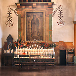 Nuestra Señora de Guadalupe, Our Lady of Guadalupe, Patron Saint of the Americas and votive candles in the mission chapel, San Juan Bautista, Calif.