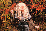 A woman dressed in a medieval gown, with long white curly hair and closed eyes, standing by among trees.