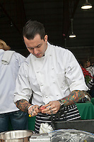 A chef with  tatooed hands as he peels a red-skinned potato at Slow Food's Picnic at the Brick Works in Toronto, 2010.