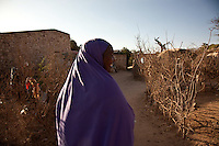 "Koos Aw Dahir - 40.Has been living in State House since 1992 .11 children - oldest, 22, youngest, 3.Koos looks after four of Siida's ( a new arrival from Mogadishu)  children...""I have 11 children and my own problems, but I was touched by the problems of Siida.  I fled Somaliland during the 1988 war in Somalia so I know the problems of a refugee.  I cannot forget the war.  There was fighting, bullets.  Our men were being slaughtered in front of us like goats.  When we fled, we were afraid of wild animals.  Hyenas are around during war - they like the taste of human flesh.""  ..""When people first arrive, they are very afraid. They still have the feeling of where they've come from.  When I look at them, it's like looking at people running out of a burning house.  The new families who come here have nothing so they rely on us.""  .. ""When it was built, State House was very beautiful.  I never went in and saw it, the closest you could get was the gate.  But people who'd seen inside used to tell stories, it was marvelous.  .There are so many problems here now though.  There is no water, no medical centre, no playgrounds for the children."".  .""I want the international community to look with a kind eye on the community living in State House.  Already we are displaced in our own country with no water, education, health services.  At the same time, we have another group of refugees adding to our problems.""."