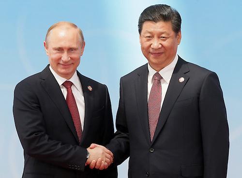 El presidente ruso, Vladímir Putin (izq), estrecha la mano a su homólogo chino, Xi Jinping