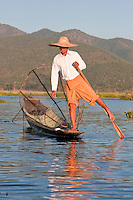 Myanmar, Burma.  Fisherman rowing his canoe with one leg, in the style common to Inle Lake, Shan State.