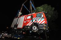 ALGEMEEN: JOURE: 25-09-2014, Brandweerauto van Joure te water, auto raakte op weg naar een verkeersongeval in een bocht aan de Haskerveldweg onbestuurbaar, oorzaak stuur blokkeerde door een helm die klem kwam te zitten, kraanbedrijf Schot takelde de auto weer op het droge, ©foto Martin de Jong
