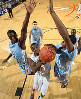 Jan. 8, 2011; Charlottesville, VA, USA;  Virginia Cavaliers guard K.T. Harrell (24) is defended by North Carolina Tar Heels forward Harrison Barnes (40) and North Carolina Tar Heels forward John Henson (31) as he shoots the ball during the game at the John Paul Jones Arena. North Carolina won 62-56. Mandatory Credit: Andrew Shurtleff