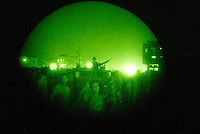 """Baghdad, Iraq, June 6, 2003.US Army soldiers on night patrol in Thawra (ex-Saddam City), the most dangerous area of Baghdad. The """"night vision"""" googles reveal a dense crowd surrounding the Hummvees and...a """"Batman"""" T-shirt!."""