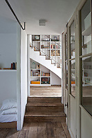 Rustic wooden steps lead from a bedroom into the staircase hall