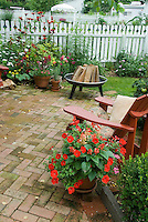 Backyard brick patio, firepit, red Adirondack chair, pots of annuals, perennials, lawn, white picket fence, several backyards