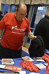 "Oct. 15, 2012 - Hempstead, New York, U.S. - Man attending Simpson and Bowles event at Hofstra puts on red shirt that Fix the Debt Campaign gives free  to anyone who puts in on right there in lobby and wears it to event at Hofstra University's John Cranford Adams Playouse., The campaign's co-founders, Simpson and Bowles, speak in the auditorium about ?America's Debt and Deficit Crisis: Issues and Solutions.? This event with the co-chairmen of the National Commission on Fiscal Responsibility and Reform, and co-leaders of Simpson-Bowles non-partisan U.S. fiscal debt reduction plan, was part of ""Debate 2012 Pride Politics and Policy"" a series of events leading up to when Hofstra hosts the 2nd Presidential Debate between Obama and M. Romney, the next night, October 16, 2012, in a Town Meeting format."