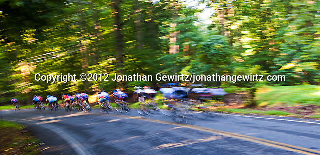 A group of recreational bicyclists passes the camera in a blur on its way down a hill in a wooded area.