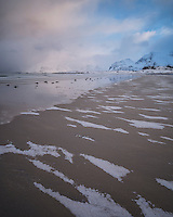 Patters of snow on sand at Ytresand beach in winter, Moskenesøy, Lofoten Islands, Norway