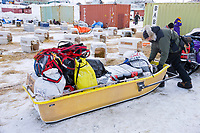 2008 All Alaska Sweepstakes 100 year commemorative sled dog race dog staging area before the start of the race in Nome, Alaska. Jim Lanier's support crew load snow machine sled with race supplies.