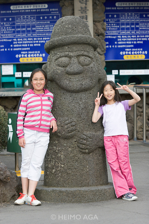 "Jeju Island. Toursit kids with a basalt Dolharubang (""stone grandfather"")."