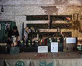 Verkäufer auf dem Schießstand der Wolfschanze. Hier sind die verschiedenen Waffen zum Ausleihen ausgestellt. Zudem kann man hier Andenken wie Handgranaten, Patronen Stahlhelme usw. kaufen. Der Schießstand ist auf dem Gelände der Wolfschanze untergebracht. Gegen Bezahlung kann man sich verschiedenste Waffen ausleihen und mit Softgunmonition schießen. / Gun range at Wolf's Lair where you can rent guns. /  Wolfsschanze, Wolf's Lair