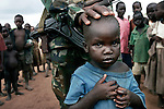 PAGAK, UGANDA AUGUST 5: A soldier from the Ugandan Army with refugee children on August 5, 2005 in Pagak, camp for displayed people in northern Uganda. About 1.5 million people have fled villages and live in about 180 squalid Internally Displaced People (IDP) camps, which has changed rural life in Northern Uganda. .Many children in this area are afraid of being abducted by the Lord's Resistance Army (LRA). The rebel group has brought terror to Northern Uganda for almost twenty years, fighting the Ugandan government. The victims are usually children, which are abducted and used as child soldiers and sex slaves. (Photo: Per-Anders Pettersson)....