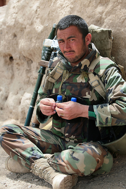 An Afghan soldier takes a break during a patrol with U.S. soldiers in the villages of Loy Kariz and Sawar Kariz in Maiwand district, Kandahar province, Afghanistan. April 9, 2009. DREW BROWN/STARS AND STRIPES