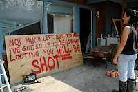 Pamela DeBaun admires her home made sign that warns looters at her Bay St. Louis home after Hurricane Katrina.