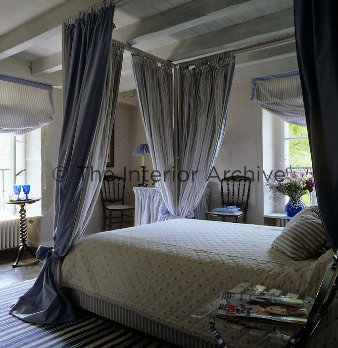 Blue and white striped textiles have been used to decorate the floor, windows and bed frame in this feminine bedroom