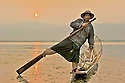 Inle lake fisherman at sunrise. Fishermen of this lake use a unique rowing style standing at the stern and wrapping one leg around the oar.