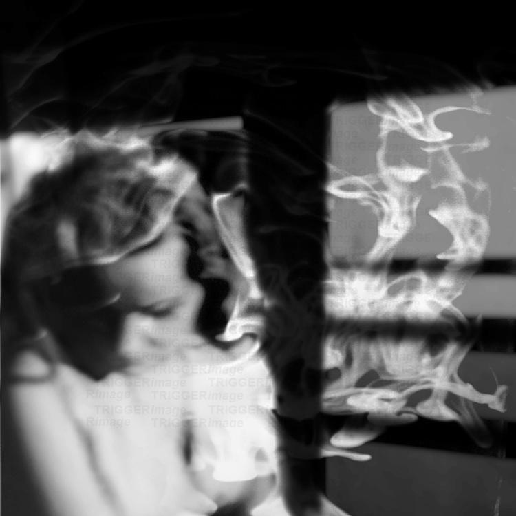 A woman looks down as smoke swirls around her