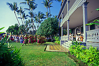 A female halau wearing traditional costumes and maile lei performs hula for tourists at Huli Hee Palace on the Big Island of Hawaii.