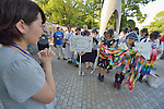 A woman prays as an delegation of children from an Anglican school deposits folded paper cranes they brought to Hiroshima in commemoration of the 70th anniversary of the U.S. dropping an atomic bomb on the Japanese city of Hiroshima. The cranes are a sign of hope and peace.