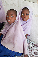 Jambiani, Zanzibar, Tanzania.  African Muslim Schoolgirls.  The Indian Ocean beach is less than a hundred feet from the classroom, explaining why grains of sand sometimes decorate the faces of the children.