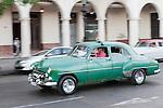 Havana, Cuba; a classic green 1952 Chevy driving along the Paseo de Marti past the Saratoga Hotel